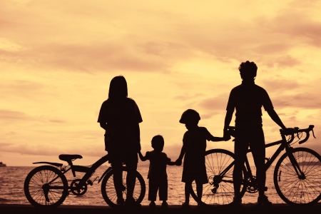 Biker family silhouette at the beach at sunet. Stock Photo - 15734043