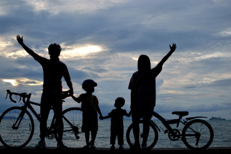 Biker family silhouette at the beach at sunet. photo