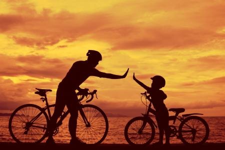 padre e hijo: Familia Biker silueta, papá e hijo en la playa de sunet. Foto de archivo