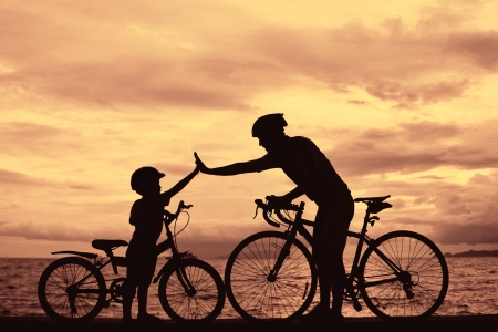 happy life: Biker family silhouette , daddy and son at the beach at sunet.