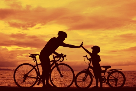 picnic: Biker family silhouette , daddy and son at the beach at sunet.