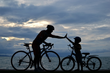 Biker family silhouette , daddy and son at the beach at sunet.