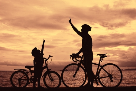 Biker family silhouette , daddy and son at the beach at sunet. Stock Photo - 15733977