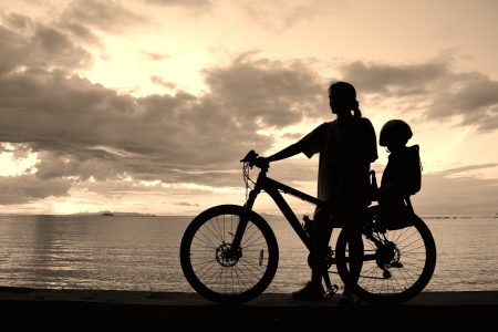 Family silhouette , daughter on child seat with parent at the beach at sunet. Stock Photo - 17064660