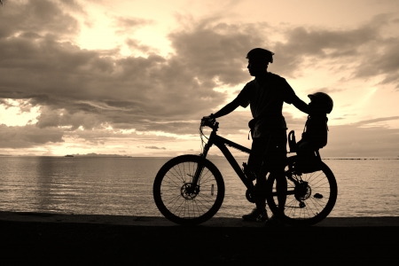Family silhouette , daughter on child seat with parent at the beach at sunet. photo