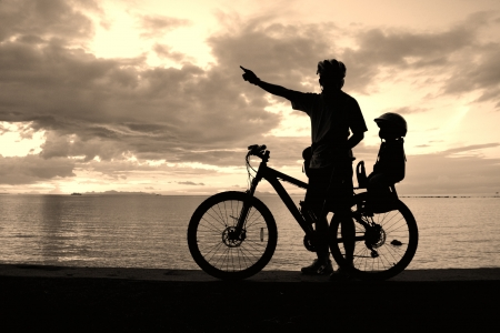 Family silhouette , daughter on child seat with parent at the beach at sunet. Stock Photo - 15733991
