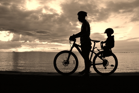 child seat: Family silhouette , daughter on child seat with parent at the beach at sunet.