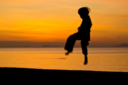 Silhouette taekwondo boy on the beach at dusk. photo