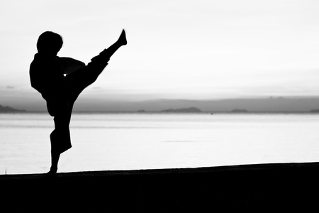 Silhouette taekwondo boy on the beach at dusk. Black and whit picture. Фото со стока