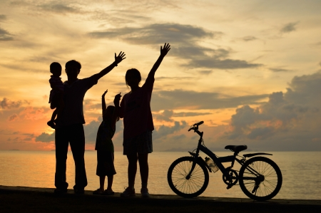 Biker family silhouette  at the beach at sunset. Stock Photo - 16155087