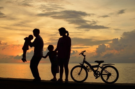 Biker family silhouette  at the beach at sunset. Stock Photo - 16155105