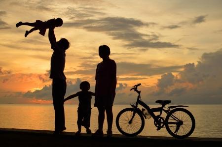 Biker silueta familiar en la playa al atardecer. Foto de archivo - 16155110