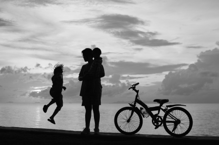 Biker family silhouette  at the beach at sunset. photo