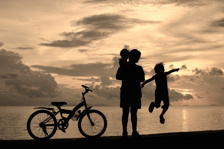 Biker family silhouette  at the beach at sunset. Stock Photo - 16155172