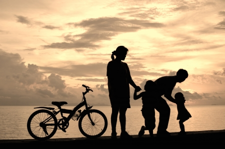 Biker family silhouette  at the beach at sunset. Stock Photo - 16155049
