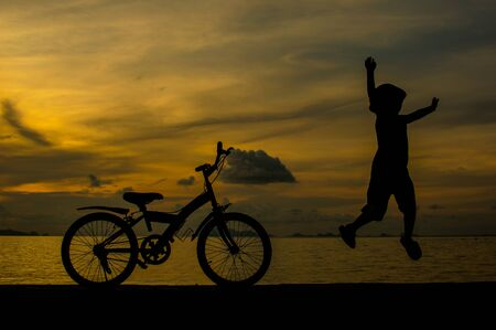 silhouette of small boy on bike at dusk. Stock Photo - 16182919