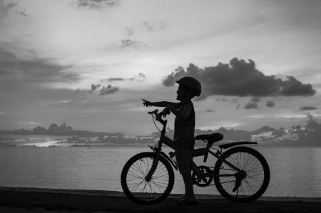 silhouette of small boy on bike at dusk. photo