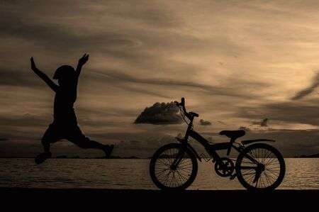 silhouette of small boy on bike at dusk. Stock Photo - 16183003