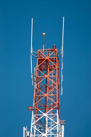 Communications tower with antennas against blue sky. photo