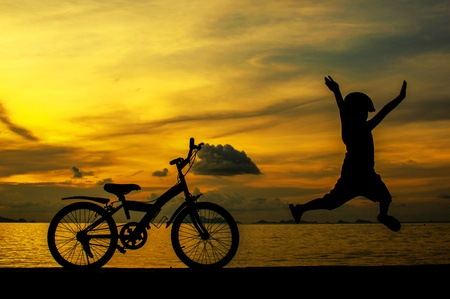 silhouette of small boy on bike at dusk. Stock Photo - 16290253