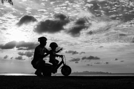 Biker family silhouette on the beach at sunset. photo