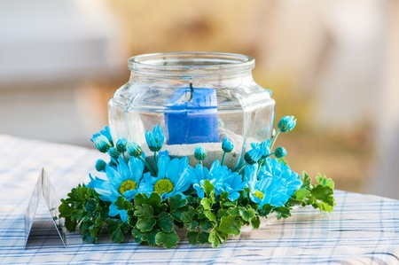 Colorful candle in vase, flower decorated on the table. photo