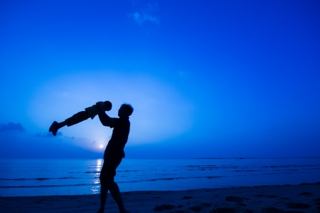 silhouette of happy man playing with daughter at the beach. photo