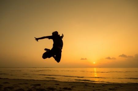 persona saltando: silueta del hombre feliz saltando en la playa. Foto de archivo
