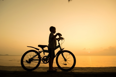 silhouette of small boy with bycycle at the beach. photo