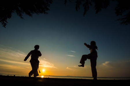 silhouette of taekwondo student during practice at sunset. photo