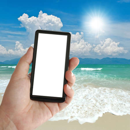 mobile phone in lady hand over seascape background. photo
