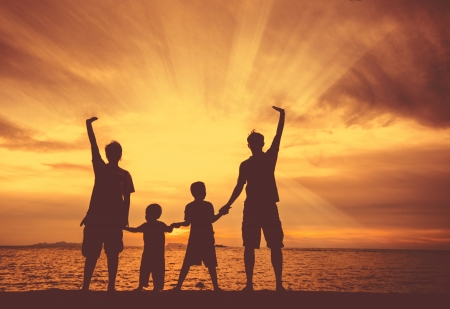 silhouette of happy family at the beach. photo