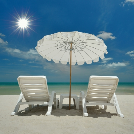white beach chair with umbrela on the beach photo