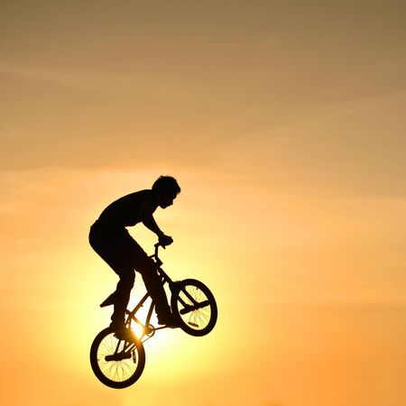 jung: bmx rider action against sky at sunset.