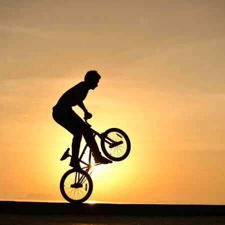 bmx rider action against sky at sunset. photo