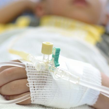 Intra venous fluid line at left arm of boy patient. Stock Photo