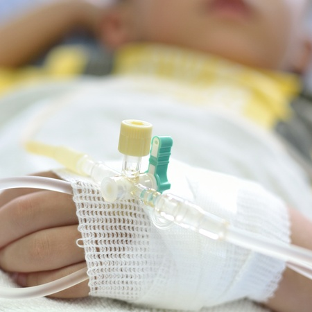 Venosa intra l?nea de flu?do en el brazo izquierdo del paciente ni?o. Foto de archivo - 21213734