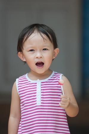 samll: Cute asian girl with samll lolipop. Stock Photo