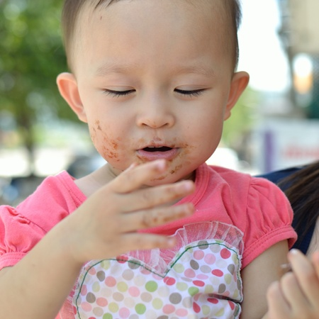 Little cute asian girl portrait with face covered in yummy chocolate wafer stick. photo