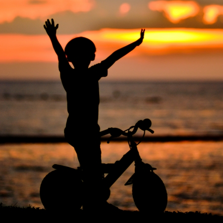 silhouette of  small boy with bicycle on the beach at dusk. photo