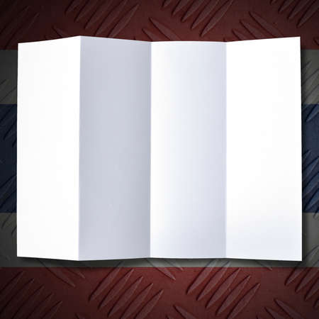 Simple folded white blank paper on the old flag background. photo