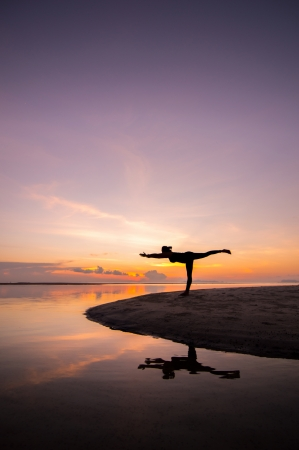 Silhouette woman with yoga posure on the beach at sunset with reflection. photo