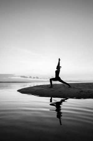 Silhouette woman with yoga posure on the beach at sunset with reflection. Stock Photo