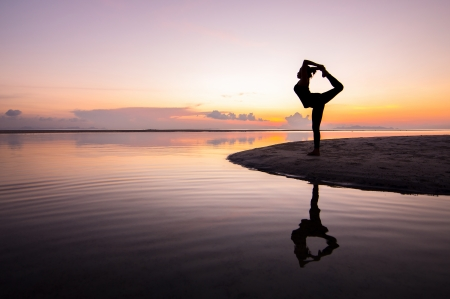 Silhouette woman with yoga posure on the beach at sunset with reflection. 版權商用圖片