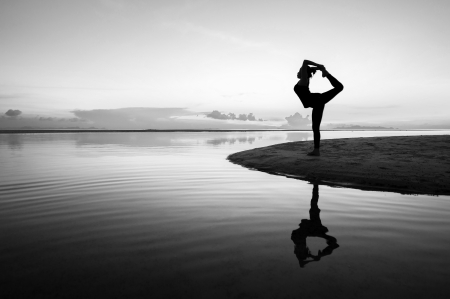 Silhouette woman with yoga posure on the beach at sunset with reflection. Standard-Bild