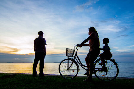 Silhouette of a biker family on the beach at dusk. photo