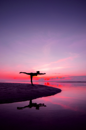 Silhouette woman with yoga posure on the beach at sunset with reflection. Фото со стока