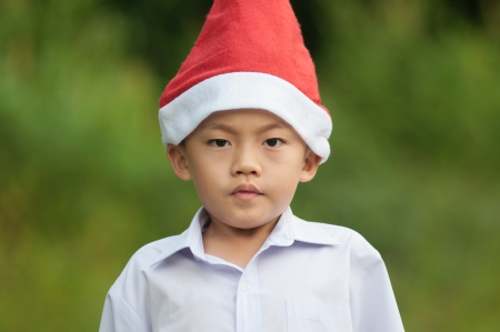 Cute asian boy with red hat and white shirt.
