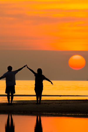 Silhouette of family on the beach during sunset. photo