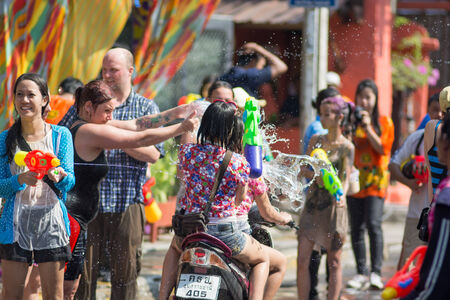 thirteen: KO SAMUI, THAILAND - APRIL 13: Foreigners and Thai people enjoy splashing water together in songkran festival on April 13, 2014 in Ko Samui island, Thailand.